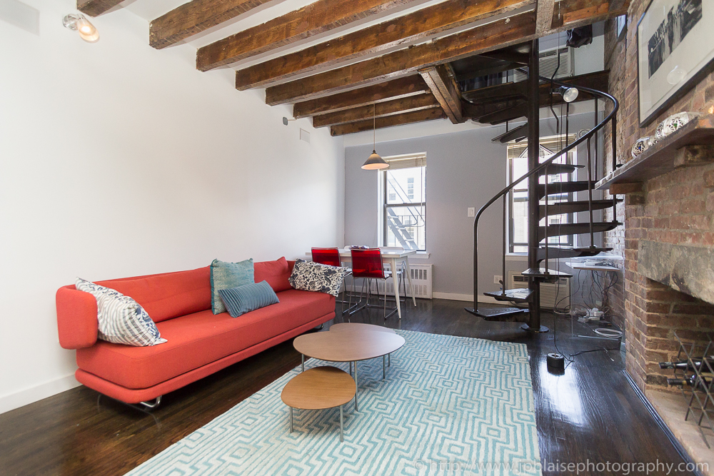 Professional photography of living room taken in the East Village of New York City, with exposed beams and brick wall